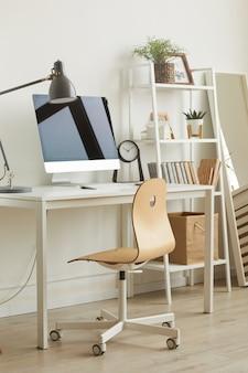 最小限のデザインで居心地の良いホームオフィスの職場、前景のコンピュータデスクに対して木製のイワナに焦点を当てる