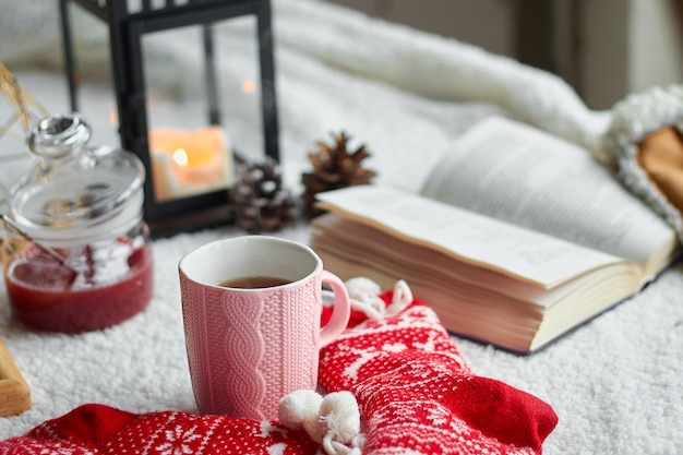 Cozy home still life cup of tea and opened book with warm plaid. winter holidays