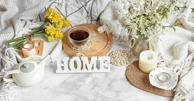 一杯のお茶とやかんのある居心地の良い家の静物。自宅のテーブルにある木製の碑文。