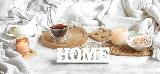 お茶とやかんのある居心地の良い家の静物。自宅での木製の碑文