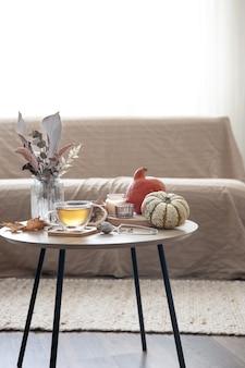 방의 흐릿한 배경에 있는 탁자 위에 차, 호박, 양초, 가을 장식 세부 사항이 있는 아늑한 집 정물.