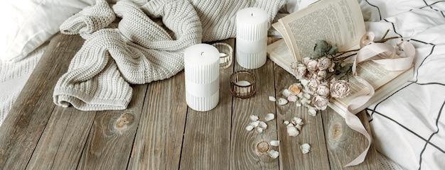 Уютный домашний натюрморт со свечами, вязанным элементом, книгой и цветами.