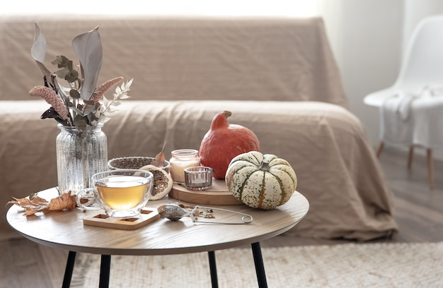 Accogliente natura morta domestica con una tazza di tè, zucche, candele e dettagli decorativi autunnali su un tavolo su uno sfondo sfocato della stanza.