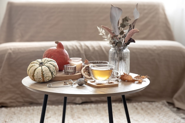 Cozy home still life with a cup of tea, pumpkins, candles and autumn decor details on a table on a blurred background of the room.