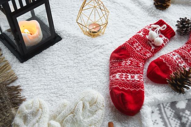 居心地の良い家庭の静物:ウールの手袋、赤いウールの靴下、コーン、暖かいウールの毛布とセーターが付いたキャンドル。冬休み