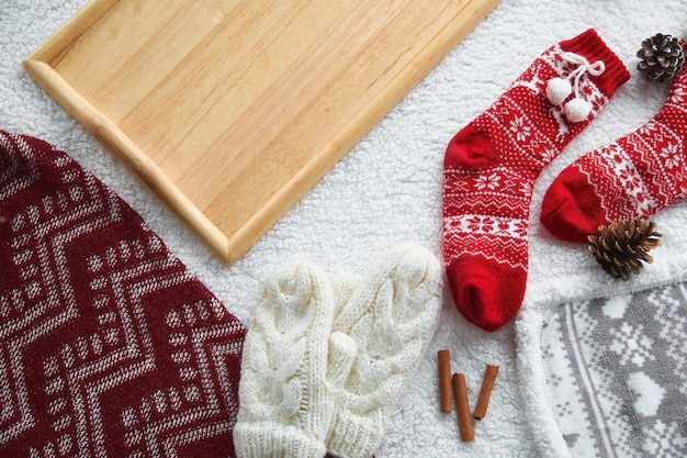 Cozy home still life: wool gloves, red wool socks, cones, candles with a warm woolen blanket and a sweater. winter holidays