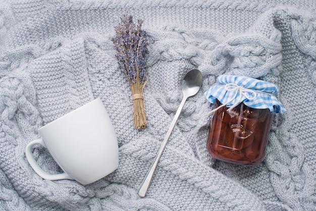 居心地の良い家、ティータイム、スプーン付きの白いカップ、ラベンダーの枝、ニットの格子縞の瓶の中のジャム。