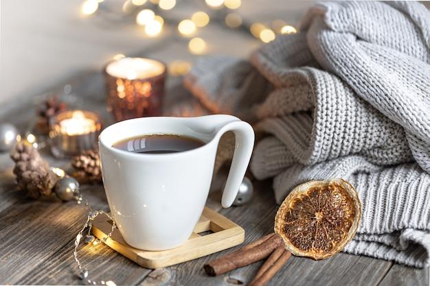 Accogliente composizione invernale domestica con una tazza di tè su uno sfondo sfocato con candele accese e luci bokeh ed elementi a maglia.