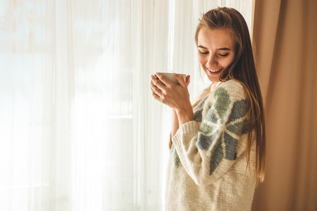 Cozy home. woman with cup of hot drink  by the window. looking at window and drink tea. good morning with tea. pretty young woman relaxing. happy concept.
