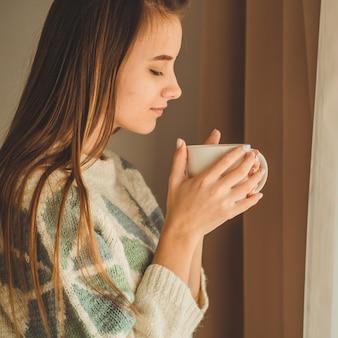 居心地の良い家。窓際に温かい飲み物のカップを持つ女性。窓を見てお茶を飲む。おはようお茶で。かなり若い女性がリラックスできます。幸せなコンセプトです。