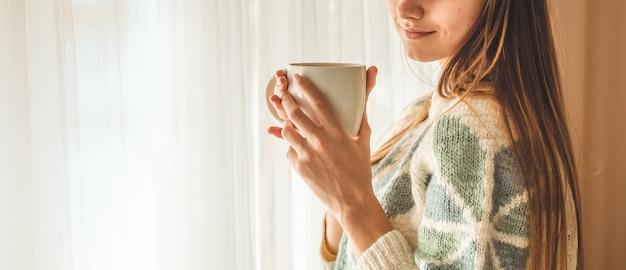 Уютный дом. женщина с чашкой горячего напитка у окна. глядя в окно и пью чай. доброе утро с чаем. довольно молодая женщина расслабляющий. счастливая концепция.