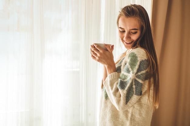 아늑한 집. 창이 뜨거운 음료 한잔과 함께 여자. 창문을보고 차를 마신다. 차와 함께 좋은 아침. 편안한 예쁜 젊은 여자. 행복한 개념.