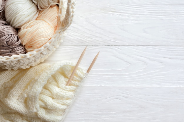 Уютная домашняя атмосфера. женское хобби - вязание. пряжа теплых тонов. розовый, персиковый, бежевый, белый и зеленый. начало процесса вязания женского свитера.