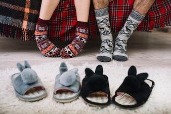 Cozy house shoes on floor near human legs