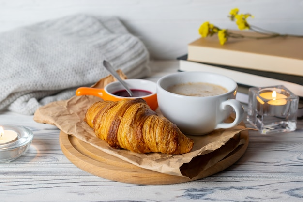 Cozy hygge composition with fresh homemade croissant and coffee on wooden table with candles, books and knitwear