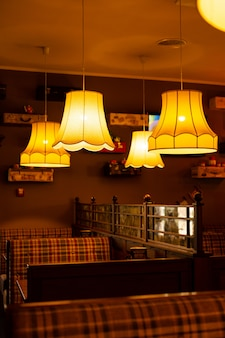The cozy interior of the cafe. warm yellow light chandeliers and checkered sofas