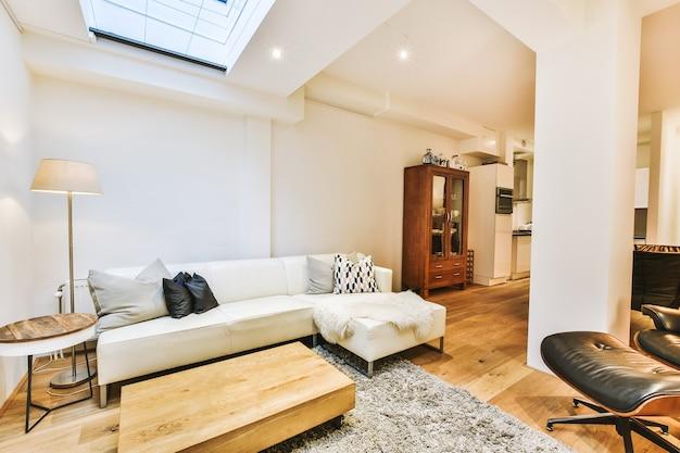 Уютный интерьер гостиной с удобным диваном и деревянным столом, украшенным ковром и лампой, в современной мансардной квартире с белыми стенами и колонной.