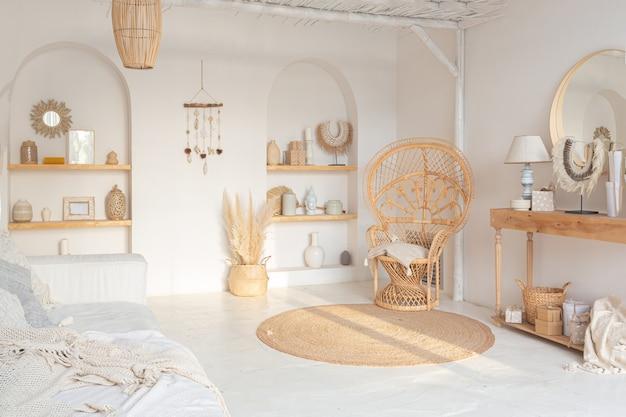 Уютный интерьер светлой квартиры в балийском стиле с белыми стенами, бамбуковым креслом, большим белым диваном и украшениями.