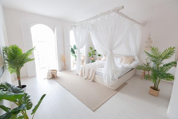 흰 벽과 대나무 가구로 꾸며진 밝은 발리 스타일 아파트의 아늑한 인테리어. 야간 조명이있는 침실, 발란 친이있는 침대 및 대형 창문