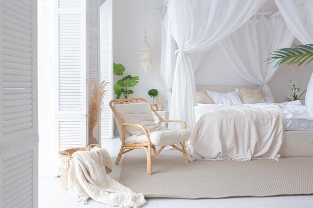 Уютный интерьер светлой квартиры в балийском стиле с белыми стенами, бамбуковой мебелью. спальная комната с ночными светильниками, кровать с баланчиной и большими окнами