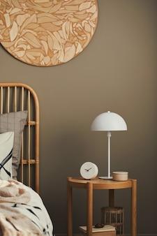 디자인 장식, 나무 침대 옆 탁자, 흰색 램프, 책, 아름다운 침대 시트, 담요, 베개 및 개인 액세서리를 갖춘 세련된 침실의 아늑한 인테리어