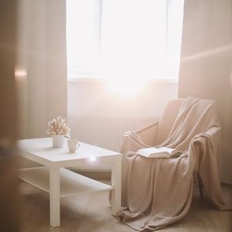 コーヒーテーブルのアームチェアと窓の近くの格子縞のある日当たりの良いリビングルームの居心地の良いインテリア