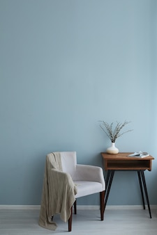 Cozy interior of retro armchair vintage wooden table with magazine and vase on it on the background of the blue wall and wooden floor.