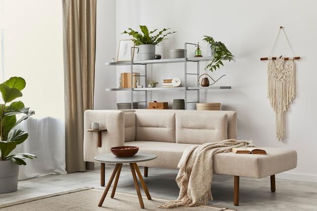 세련된 소파, 회색 커피 테이블, 책장, 식물, 카펫, 장식, 베이지 마크라메 및 우아한 개인 액세서리가있는 아늑한 인테리어. 클래식 하우스의 중립 거실.