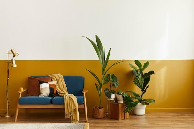Уютный интерьер со стильным бархатным диваном, деревянным кубом, ковром, декором, копией пространства, множеством растений и элегантными личными аксессуарами. современная гостиная в классическом доме ..