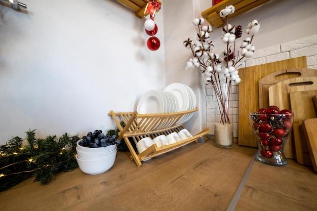나무 작업 표면에 크리스마스 접시 건조기를 위해 장식된 아늑한 주방