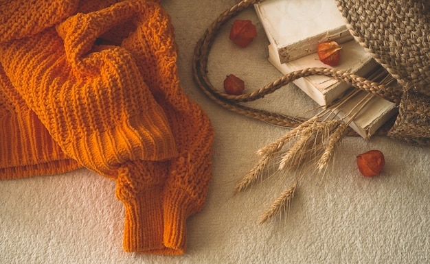 Уютный вязаный теплый оранжевый свитер со старинными книгами и винтажной соломенной сумкой на белом теплом пледе с тыквой, физалисом, осенними книгами и чтением. осеннее настроение. осень зимняя пора.