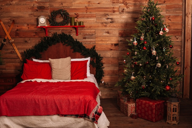 A cozy large double bed next to the christmas tree on a holiday evening