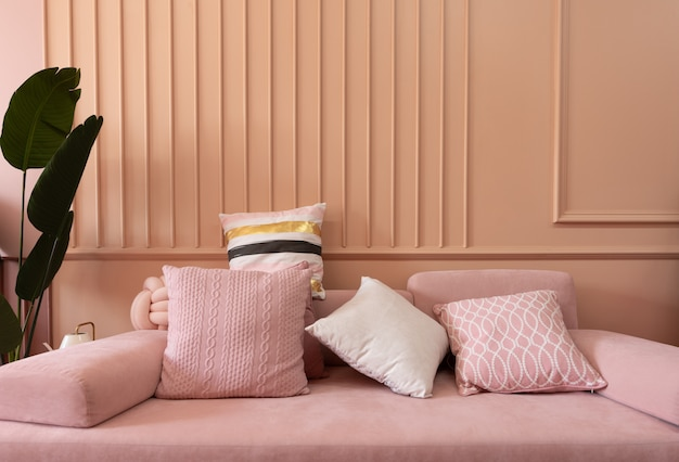 Cozy living room corner with pink sofa covered with comfortable pink pillows on decorated wall