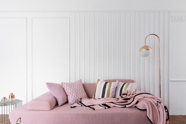 居心地の良いリビングルームのコーナーには、ピンクのベルベットのソファと、白い木製のストライプの壁にピンクのふわふわのブランケットを重ねたモダンクラシックスタイルのゴールドのフロアランプ