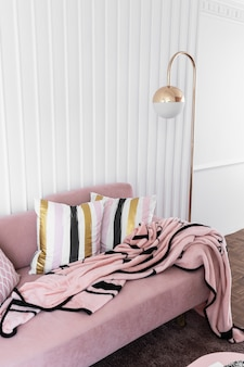 Cozy living room corner with pink velvet sofa and gold floor lamp in modern classic style on top with pink fluffy blanket with white wooden stripe wall