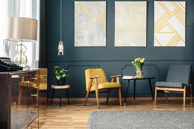 Интерьер уютной гостиной с креслами, ковриком на полу, цветами на столе, растениями и картинами