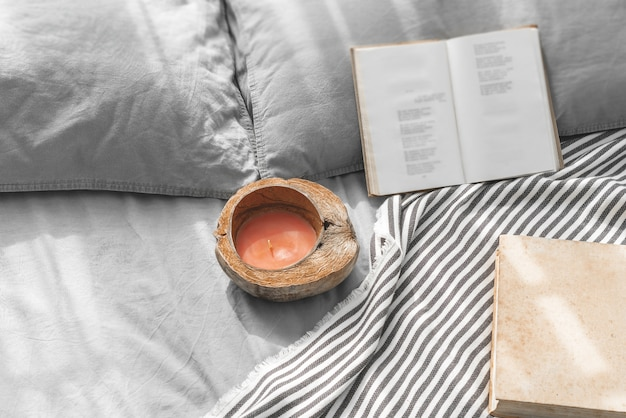 Cozy messy bed with two pillows, gray bed linen with books and coconut shell candle.