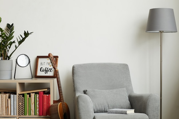 Cozy modern interior with minimal decor items and grey armchair against white wall