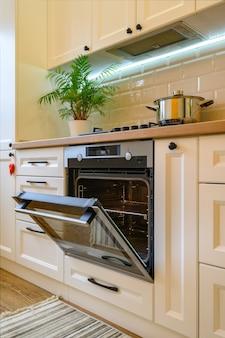 Cozy modern kitchen interior closeup to open ovens door
