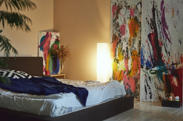 Cozy modern living room interior with abstract art paintings bed and floorlamp