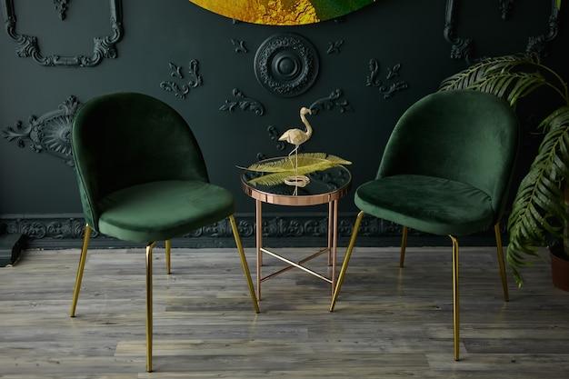자연광이 들어오는 황금색 스테인리스 거울 테이블과 벨벳 의자가있는 아늑하고 현대적인 좌석 공간입니다. 현대적인 스타일의 진한 녹색 인테리어 컨셉