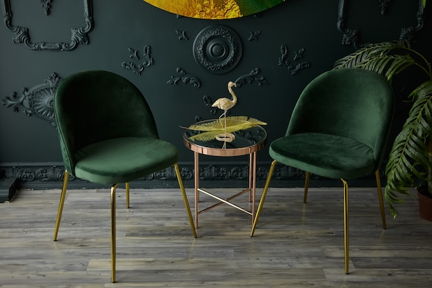 Cozy modern seating space with golden stainless mirror table and velvet chairs in natural light ambient. dark green interior concept in modern style