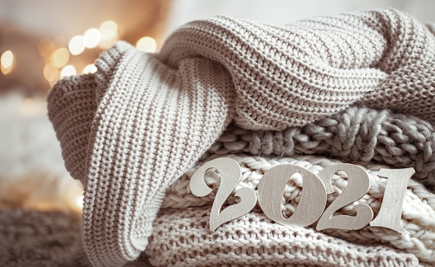 Cozy new year composition with knitted pastel colored wooden numbers 2021