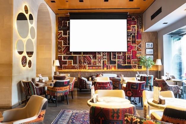 레스토랑의 아늑한 옛 스타일 인테리어, 흰색 프로젝터 스크린이있는 찻집