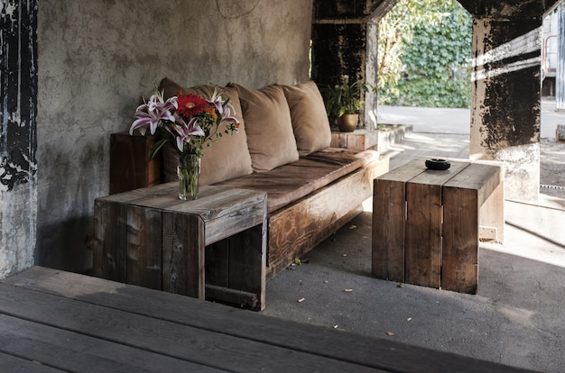 Cozy outdoor bench with pillows and a table