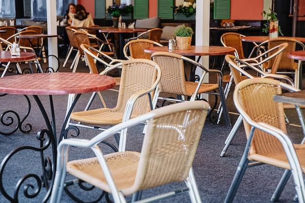 Уютное летнее кафе под открытым небом. плетеные стулья и столы в пустом ресторане под открытым небом. спокойное и романтическое место для встреч, свиданий. ретро дизайн