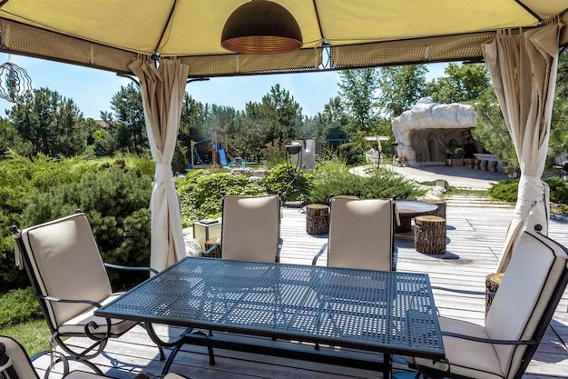 정원 텐트에 식탁과 푹신한 의자가 있는 아늑한 파티오와 화창한 여름날 시골 맨션의 잘 손질된 녹색 뒤뜰에 있는 바비큐 공간