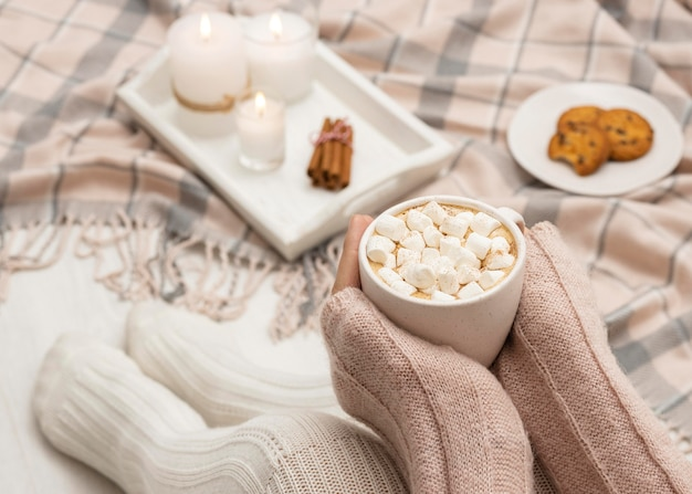 Cozy person holding mug with hot cocoa and marshmallows