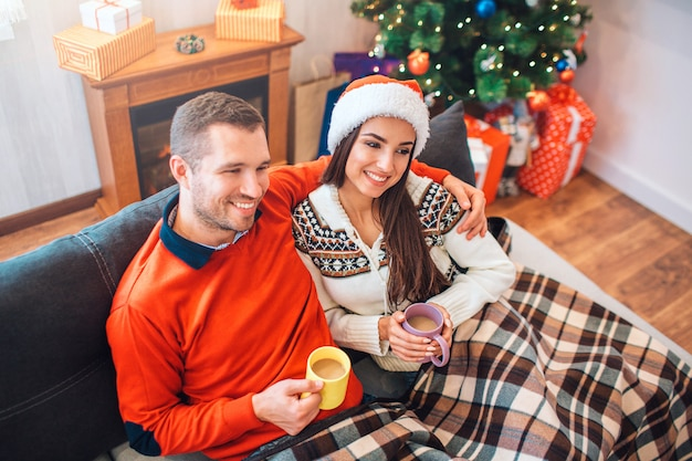 Cozy picture of happy young man and woman sitting on sofa and hold cups with hot drink.