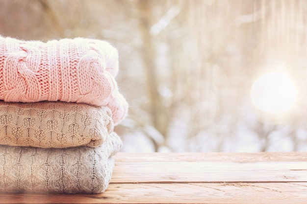 Cozy pile of wool knitted sweaters on wooden table on winter background